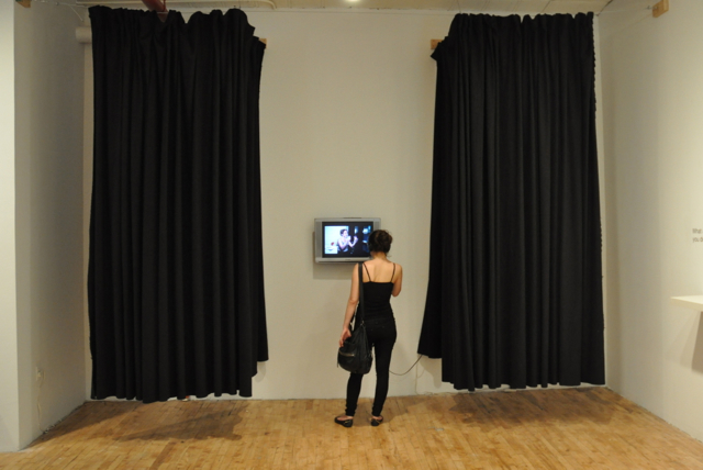 A visitor watches a video at Chloë Bass's The Bureau of Self-Recognition exhibition at Momenta Art.