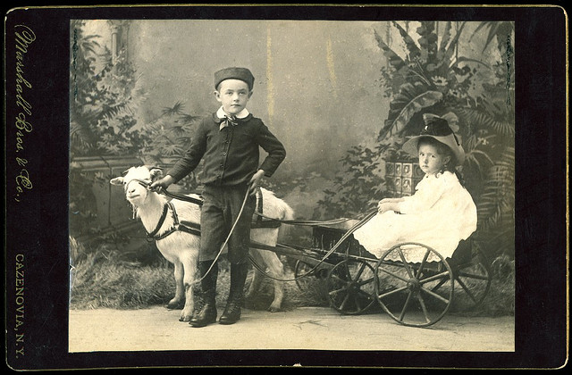 Children with a live goat and a garden backdrop (via George Eastman House)