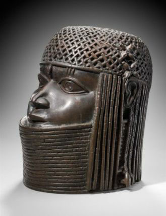 """This work by an unidentified artist, """"Commemorative head of a king (Oba),"""" Edo peoples, Benin kingdom, Nigeria (late 16th century), copper alloy, iron, 9 1/2 x 6 1/2 in (24.1 x 16.5 cm), is currently on view at the Museum of Fine Arts, Boston, but Nigeria wants it back. (image via mfa.org)"""