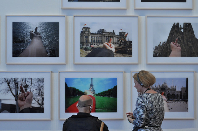 """Museum visitors in front of some of the images in Ai Weiwei's """"Study of Perspective"""" (1995-2011) series, 40 photographs"""