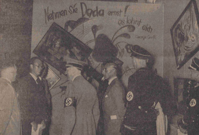 Adolf Hitler and other Nazi officials (Hoffmann, Willrich, Hansen, and Ziegler) standing by the Dada wall at the 'Entartete Kunst' (Degenerate Art) exhibition, July 16, 1937. Paintings by Vasily Kandinsky, Paul Klee, and Kurt Schwitters have been deliberately hung askew and are accompanied by a slogan penned by George Grosz. This photo was published in the Nationalist Observer, South German (Süddeutsche) issue, No. 199, July 18, 1937. (Staatsbibliothek zu Berlin Stiftung Preussischer Kulturbesitz, Berlin, Germany; bpk, Berlin, Art Resource, NY)