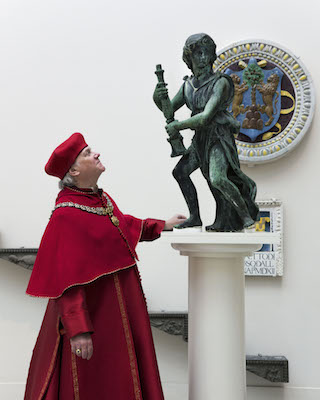Actor Paul Jesson as Cardinal Wolsey with the reunited four bronze angels (courtesy  Victoria and Albert Museum, London)