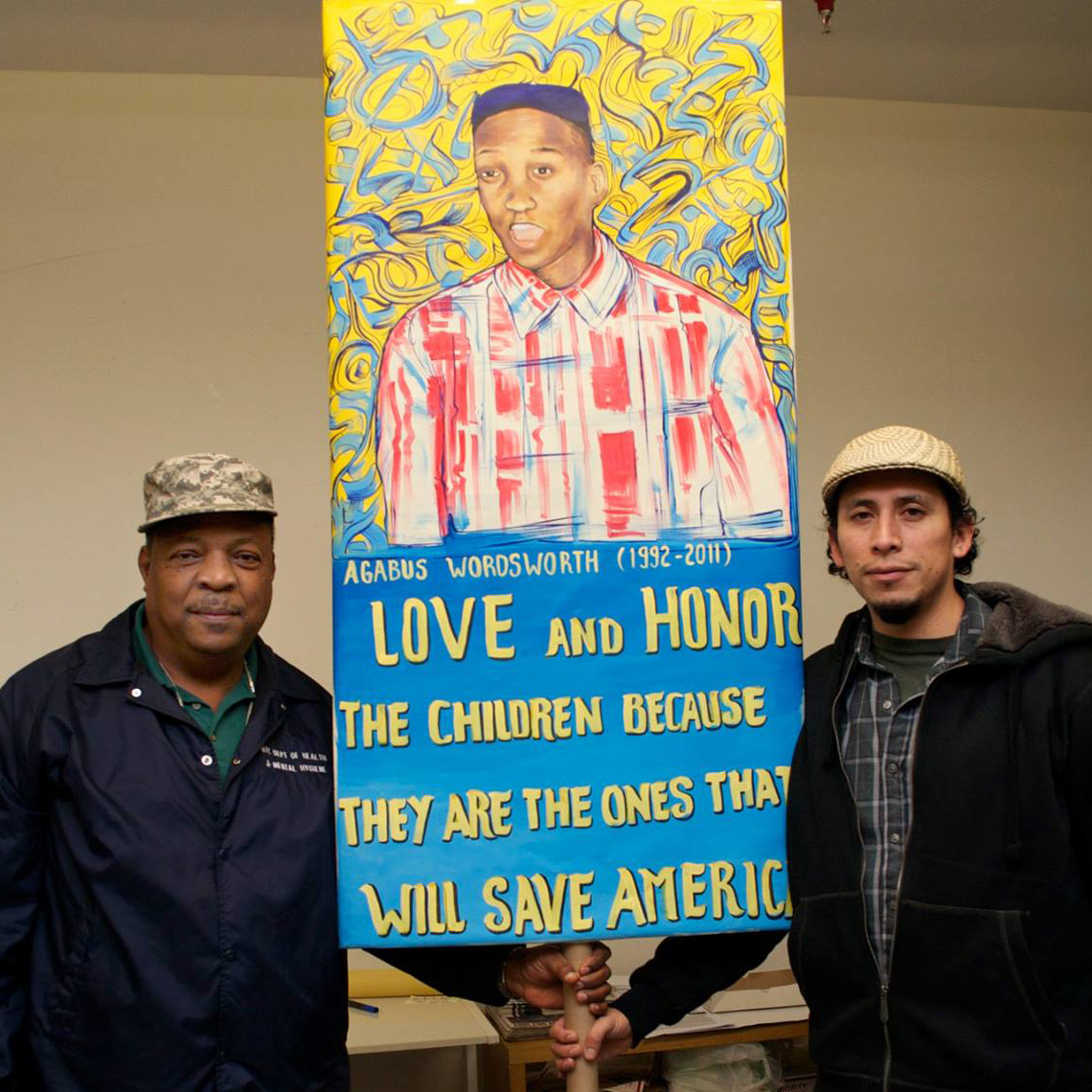 People's Climate Arts member Raul Ayala with Emboya Wordsworth who lost his son to Police Brutality. Sign made by Raul for O22 day of action. (photo courtesy People's Climate Arts)