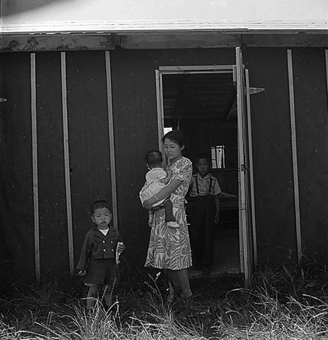 Stockton, CA, May 19, 1942. A family in front of their barracks, Stockton Assembly Center, California (Photographed by Dorothea Lange, WRA / Courtesy of the National Archives and Records Administration (National Archives Identifier 537735))