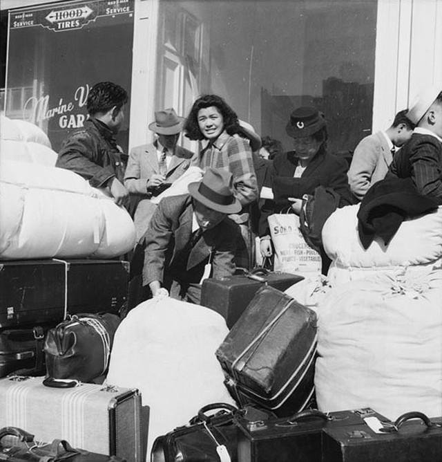 San Francisco, April 16, 1942. Americans of Japanese descent from the first contingent of 664 from awaiting buses at Van Ness Avenue to be transported to Santa Anita Park assembly center at Arcadia, California. Photo by Dorothea Lange, WRA / Courtesy of the National Archives (National Archives Identifier 536417)