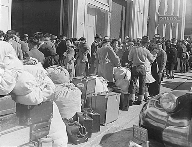 April 6, 1942, San Francisco. Japanese and Japanese Americans await a bus with the belongings they were allowed to bring at the WCCA station on Van Ness Avenue, part of the first group of 664 to be evacuated from the city (Photo by Dorothea Lange, WRA / Courtesy of the National Archives, Records of the War Relocation Authority (National Archives Identifier 536065))