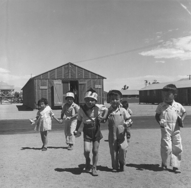 Manzanar, CA, July 1, 1942. Preschoolers on the way to their barrack homes from morning class at the camp 220 miles north of L.A. The camp was later made famous by books like Jeanne Wakatsuki Houston's 1973 Farewell to Manzanar (Photographed by Dorothea Lange, WRA / Courtesy of the National Archives via the National Park Service)