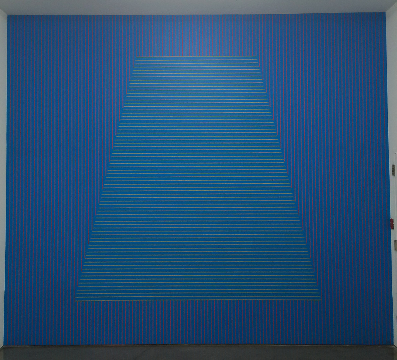 """Sol LeWitt, """"#333: On a blue wall, red vertical parallel lines, and in the center of the wall, a trapezoid within which are yellow horizontal parallel lines. The vertical lines do not enter the figure"""" (May 1980) at Gladstone Gallery"""