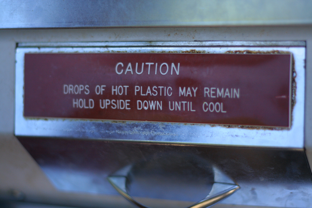 Caution sign on a Mold-A-Rama machine at the Oklahoma City Zoo in 2010 (photo by Kelly Teague/Flickr)