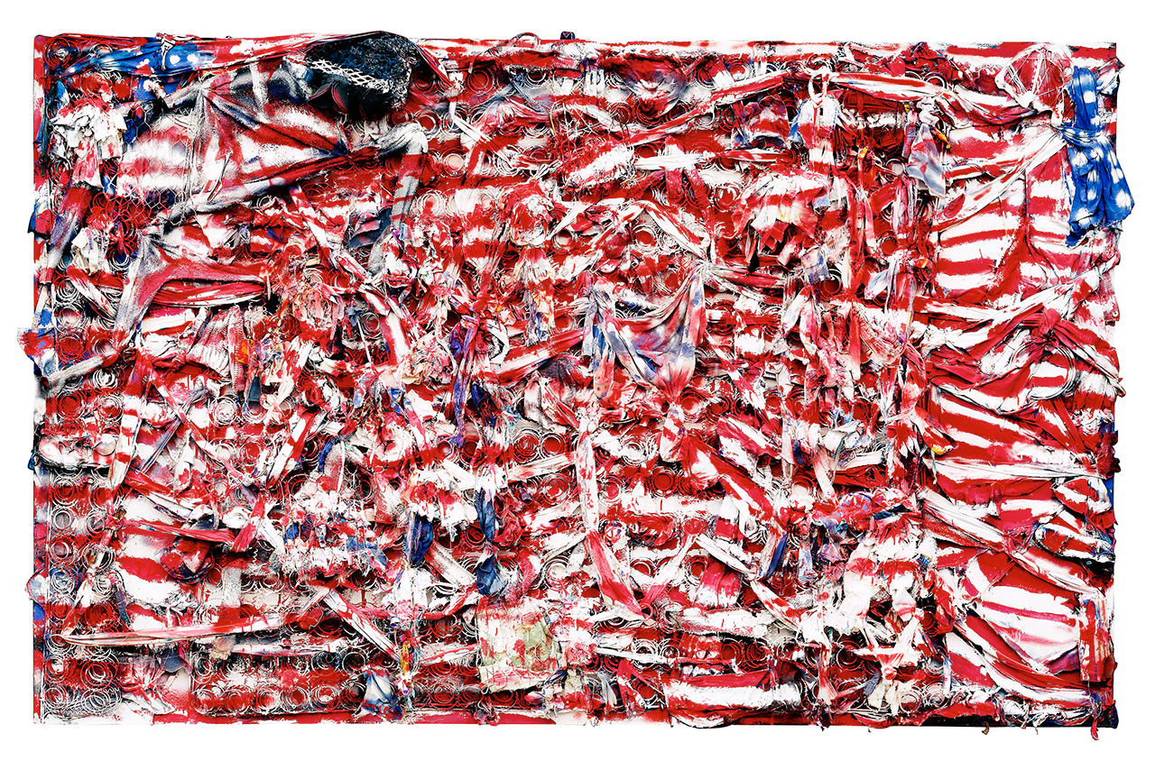 """Thornton Dial, """"Don't Matter How Raggly The Flag, It Still Got To Tie Us Together"""" (2003), mattress coils, chicken wire, clothing, can lids, found metal, plastic twine, wire, Splash Zone compound, enamel, and spray paint on canvas on wood, 71 x 114 x 8 inches, collection of Indianapolis Museum of Art (photo by Stephen Pitkin/Pitkin Studio, courtesy Souls Grown Deep Foundation) (click to enlarge)"""