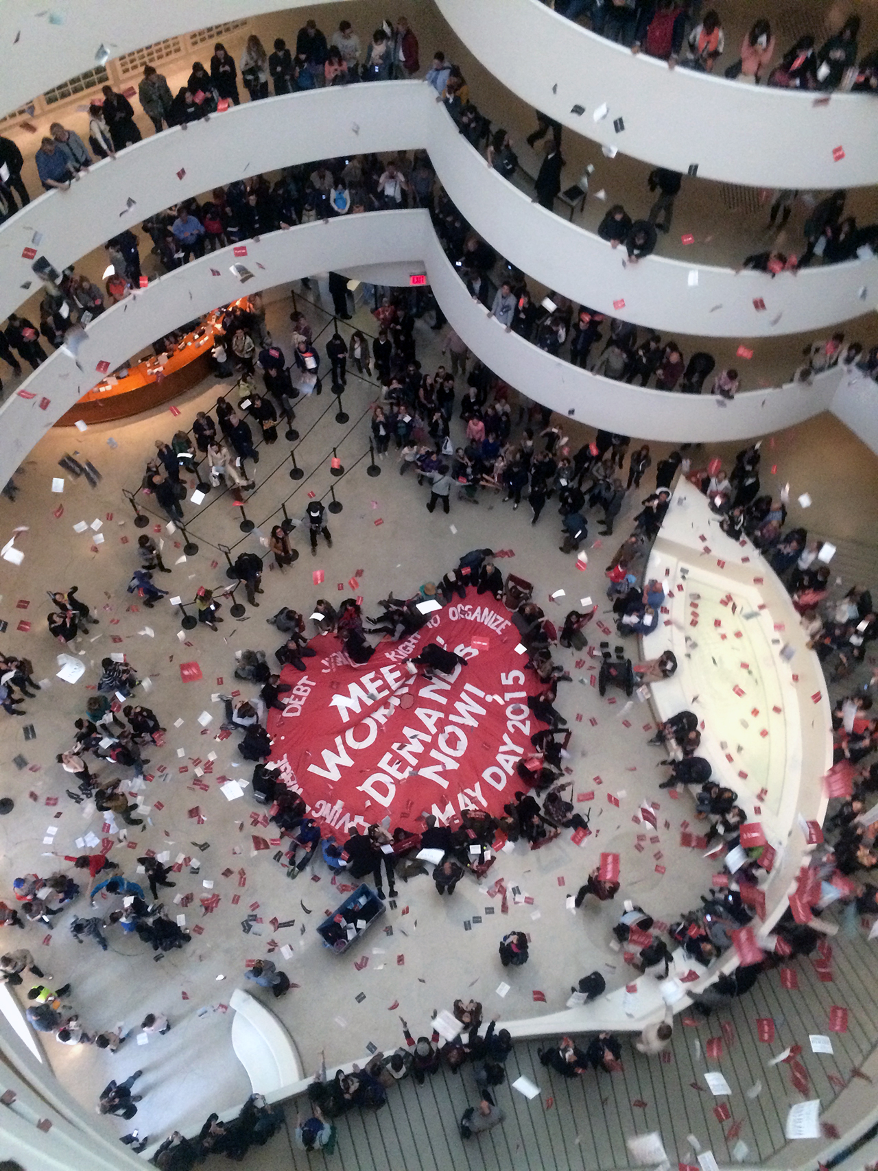 """On May Day 2015, members of the Gulf Ultra Luxury Faction (G.U.L.F.) unveiled a large parachute in the Guggenheim Museum rotunda with the words """"Meet Workers Demands Now"""" (image Benjamin Sutton/Hyperallergic)"""