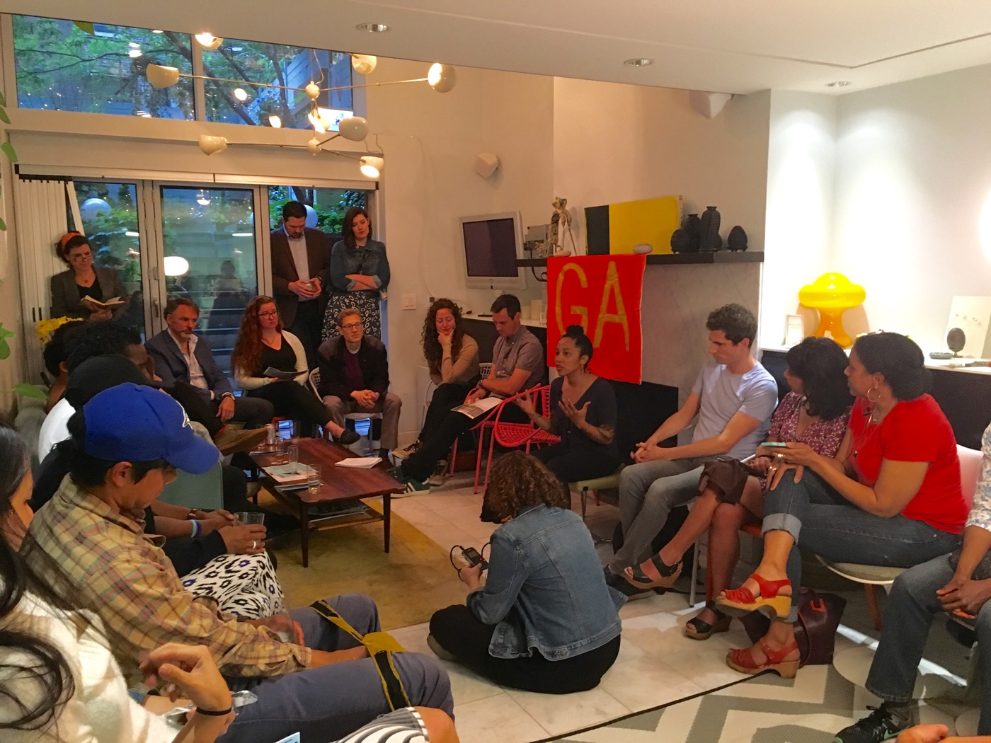 Gentrifiers Anonymous Meeting Saturday, May 14, in Chelsea. One of the organizers, Oasa DuVernay is in the center, beneath the GA flag. Photos courtesy of Jeff Kasper of More Art