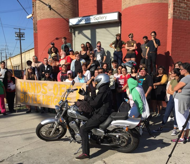 A gallery worker arrived on her motorcycle during the press conference.