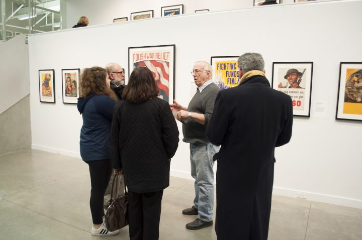 Collector Hal Wert talk with visitors about the exhibition <em srcset=