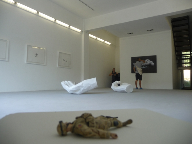 An America's Army action figure composed of multiple action figures' parts lies in the corner of the exhibition.