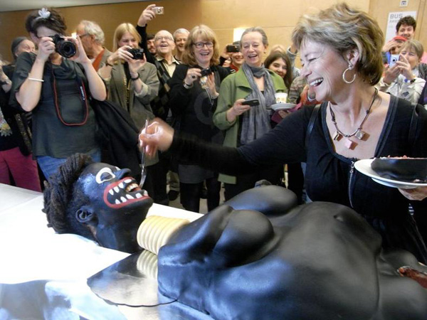 A photo of the Swedish minister feeding the artist some of the cake (image via friatider.se via Facebook)