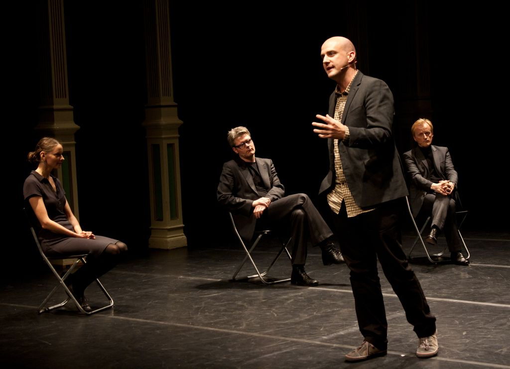 """Image from an earlier iteration of Tea Tupajić and Petra Zanki's """"The Curators' Piece (A Trial Against Art)"""" with Vallejo Gantner speaking to the audience, and seated (from left to right) Gundega Laiviņa, Florian Malzacher, and Per Ananiassen. (photo by Monica Santos Herberg)"""
