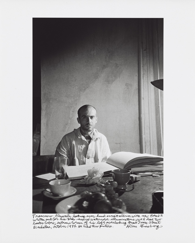 """Allen Ginsberg, """"Francesco Clemente looking over hand-script album with new poem I'd written out for his Blake-inspired watercolor illuminations, we'd done two books before; entrance corner of his loft overlooking Great Jones Street Manhattan, October 1984. He liked this picture."""" (1984) Gelatin silver print, printed 1984–97 15 7/8 x 10 5/8 in. (40.4 x 27 cm)"""