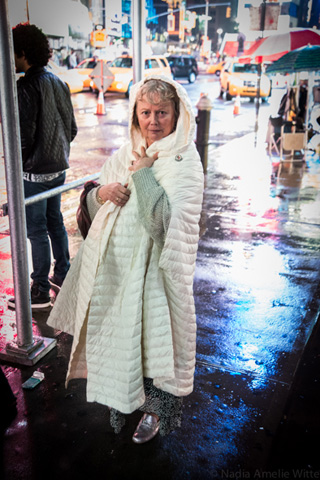 Curator Alana Heiss captured in the slick rain and glowing lights of Times Square on her way to the party. (photo by Ka-Man Tse for @TSqArts)