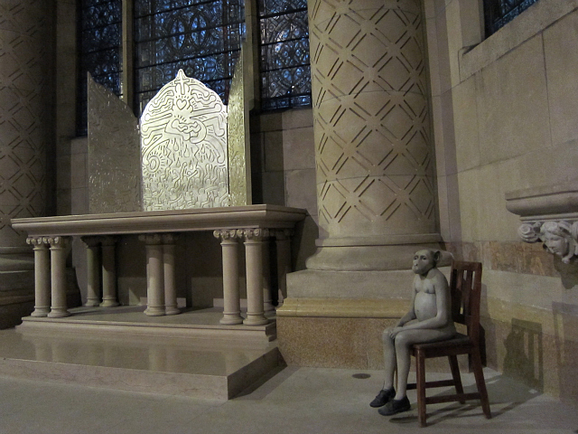 """Jane Alexander, """"Harvester"""" (1997-98), plaster, oil paint, wood chair, with St. John the Divine's triptych altar piece by Keith Haring"""