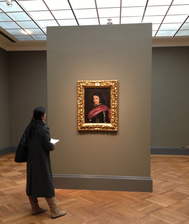 """A woman gazing at Diego Velázquez's """"Duke Francesco I d'Este"""" (1638) at the Metropolitan Museum of Art. (photo by the author for Hyperallergic)"""