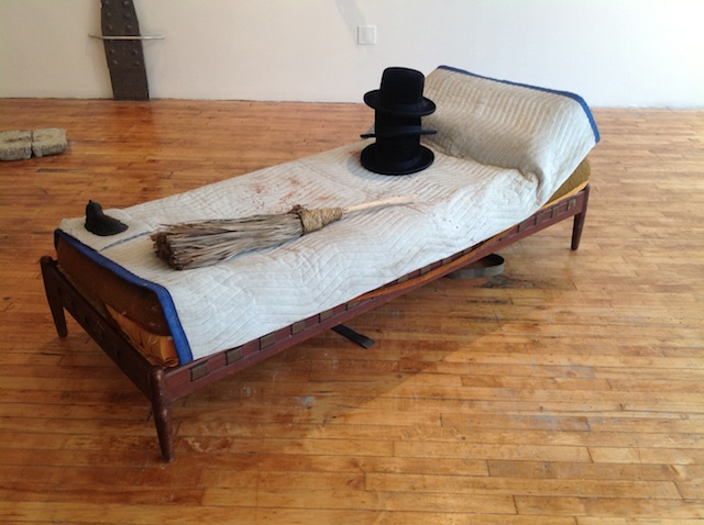 """Matt Freedman, """"Hats and Broom on Bed with Drinking glass Reflecting Full Moon"""" (2013). Epoxy  plastic, found objects, 36 x 72 x 18 inches."""