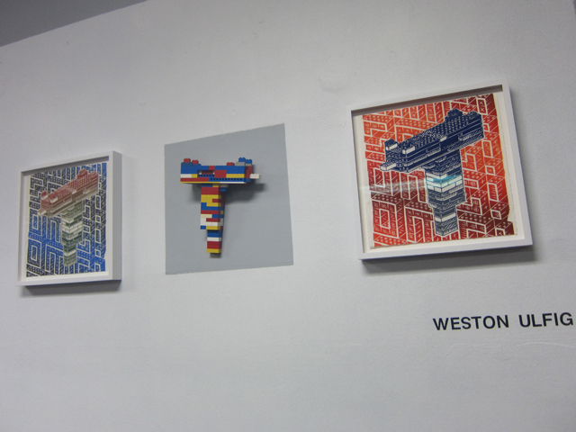 """Prints and a lego gun by Weston Ulfig, also part of the """"Magic Kingdom"""" exhibition"""