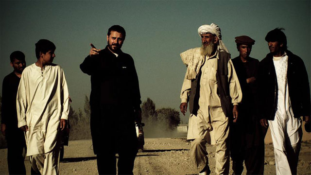 """Jeremy Scahill walking with villagers in Gardez, Aghanistan in a film still from """"Dirty Wars,"""" directed by Richard Rowley"""
