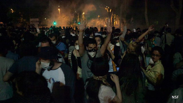 Unintimidated protesters slowly move back from police teargas. (photo: Nazim Serhat Firat, and used with permission)