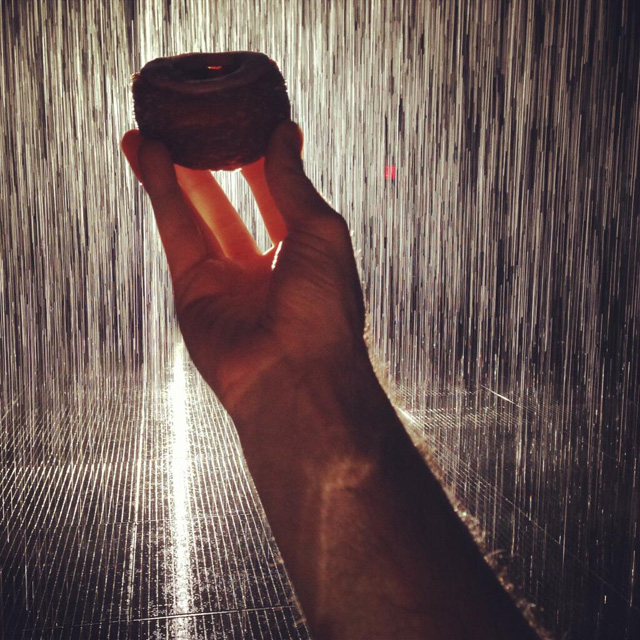 This photo that Dominique Ansel tweeted of a cronut held up inside the Rain Room captures the insanity of summertime trend waiting. (photo by Dominique Ansel on Twitter)