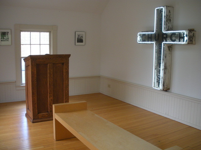 A room in the back displays the original cross — fittingly bordered in neon — and other artifacts from the church.