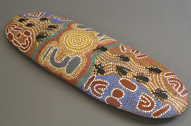 A beantree wood shield from Yuendumu, Northern Territory by Paddy Japaljarri Stewart, featuring a dot-style design in acrylic paint on the front. The artist, Paddy Japaljarri Stewart, is kirda (owner) of the story it shows.