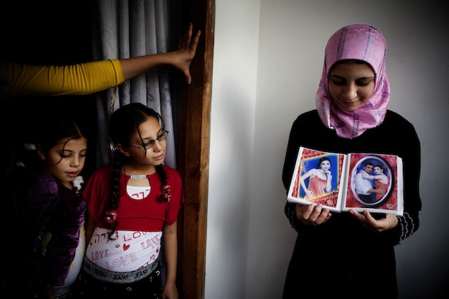 """Tanya Habjouqa, from the series """"Women of Gaza."""" Text for the photograph: """"In the Gaza City home of Dr Jamal Shareef, a literature professor at Al Azhar University, his 16-year-old niece (R) shows pictures of her fiancé."""""""