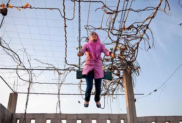 """Tanya Habjouqa, from the series """"Women of Gaza."""" Caption: """"Young girl relaxes at her family farm """"vacation"""" spot on the outskirts of Gaza city. Travel is next to impossible for the majority of Gazans due to the siege, but the Palestinians remain creative and hopeful. BBQs with the family remains a top day off from school for these young girls."""""""