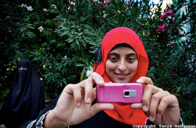"""Tanya Habjouqa, from the series """"Women of Gaza."""" Text: """"An English literature student at the Islamic University in Gaza takes a break with fellow students. She is eager to apply her English skills and says that her dream is to travel the world. The siege on Gaza makes travel near impossible for the vast majority of Gazans."""" (all images courtesy of the artist unless otherwise noted)"""