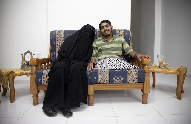 """Tanya Habjouqa, from the series """"Women of Gaza."""" Text for the photograph: """"Moemen Faiz, a photographer, sits with his new wife, Deema Ayideh, at the couple's home in Gaza. Faiz was injured during Israel's assault on Gaza in the winter of 2008-09, and was later flown to Saudi Arabia where he received treatment. The two fell in love when Ayideh, a journalist, interviewed Faiz at the hospital, and they married soon after."""""""