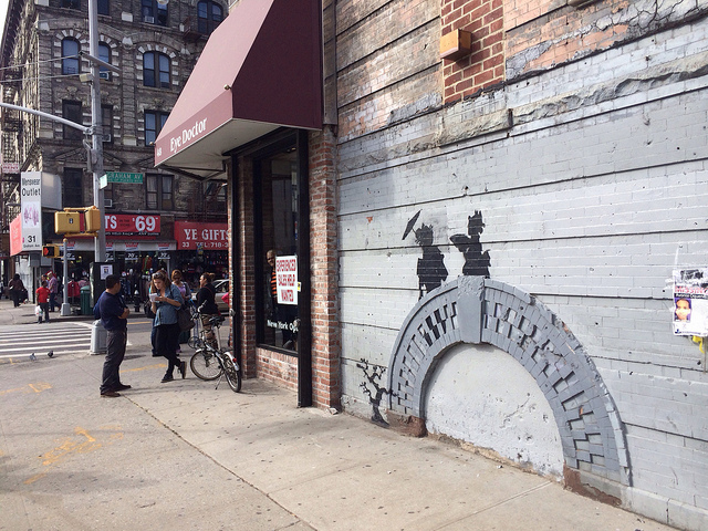 Building supervisor Feliciano Perez being interviewed by a reporter as he stands guard by the Banksy.
