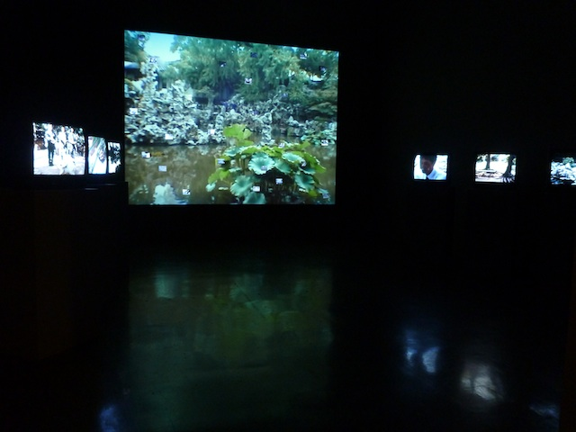 The Tonight Moon installation, with a projection, tv monitors and tiny LCD screens embedded in the projection wall. Images by the author for Hyperallergic.