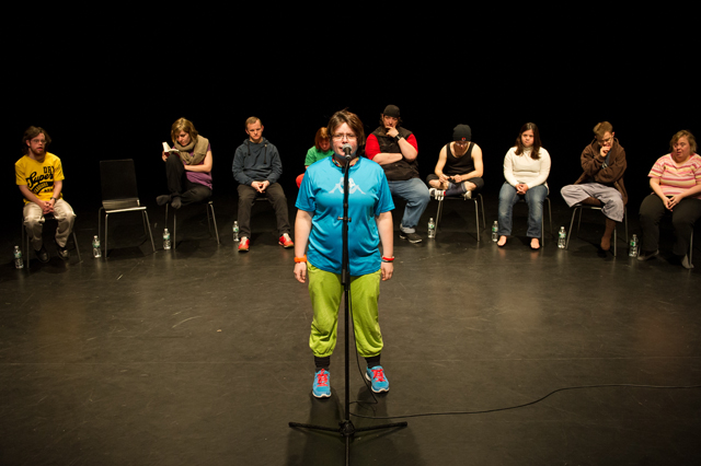 Performer Sara Hess stands at the microphone during a performance of Jerome Bel's Disabled Theater. (Photo: Ian Douglas; Courtesy: New York Live Arts)