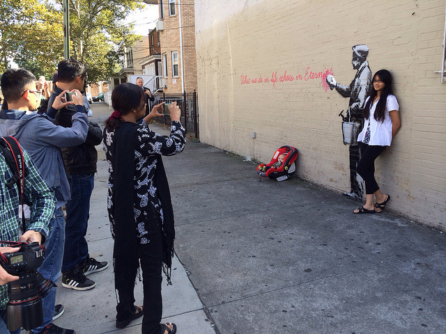 """There's something about Banksy that tells people to """"bring their kids along"""" and capture the moment."""