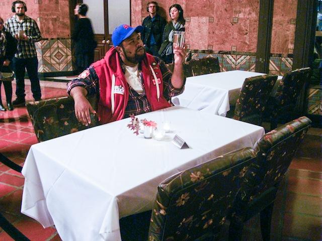 Marco Polo (played by Ashley Faatoalia) at Traxx Restaurant.