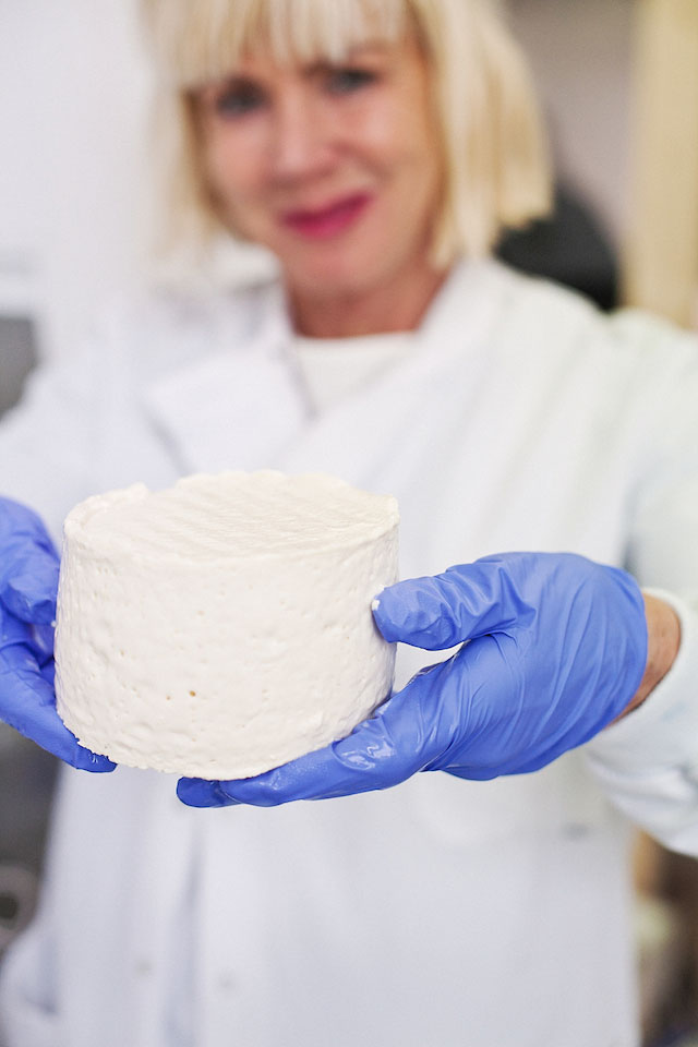 """Sissel Tolaas holds a cheese that is left to age. (Selfmade by Christina Agapakis and Sissel Tolaas is part of """"Grow Your Own: Life After Nature"""" at Science Gallery at Trinity College Dublin)"""