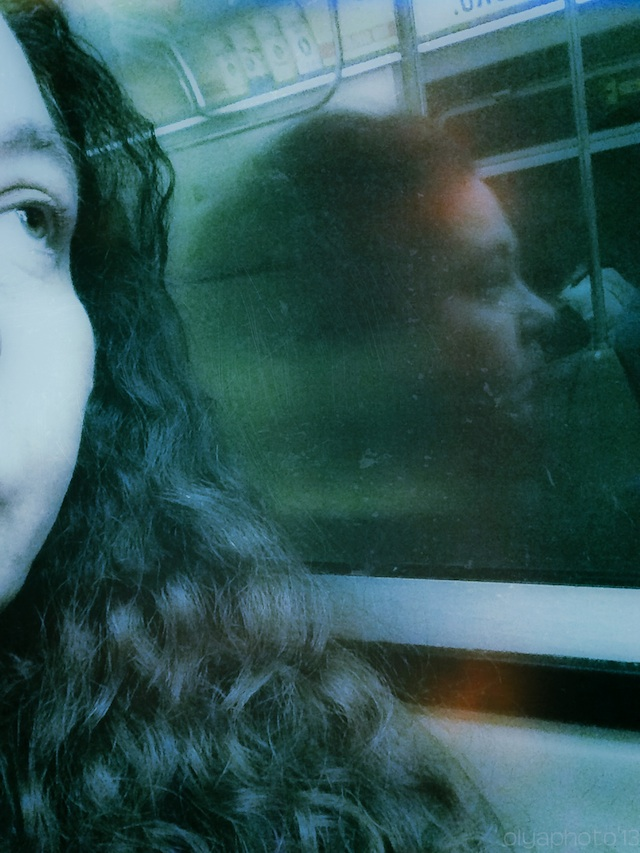 """Olya Turcihin's subway selfie: """"When I am on the subway, the act of taking pictures of myself and well as other passengers makes the time go by in a surrealist fashion."""""""