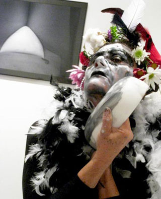 """Angela Freiberger mixing face paint with her sculpture """"PwE (Plate with Eye)"""" (2010);  her photograph """"Vulva Place"""" (2010) hangs overhead. (click to enlarge)"""