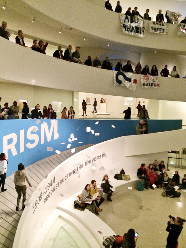 Flyers raining down onto the floor of the Guggenheim Museum in Manhattan, while protesters and chant and hold banners over the railings of the museum. (all photos by the author for Hyperallergic)