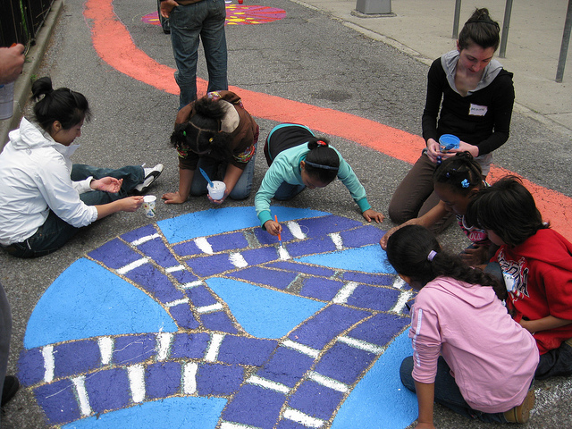 Brooklyn-based muralist Ellie Balk collaborated with art teacher Leslie Elvin and her students to design a colorful abstract map with a striped path that meanders through circle mandalas and reflects drawings made by the students after learning about street safety. (photo via NYC Dept. of Transportation's Flickrstream)