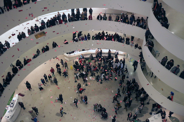Dollar bill leaflets rain down Guggenheim rotunda at 6:45 pm (all photographs by the author for Hyperallergic)