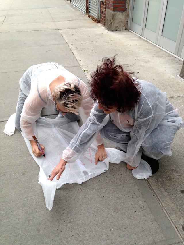 Christen Clifford (left) and Karen Malpede (right) writing on a jumpsuit (click to enlarge)