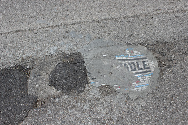 One of Bachor's mosaics that has been nearly swallowed by its neighboring potholes and cement fill-ins