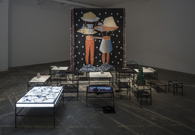 """Otobong Nkanga, """"In Pursuit of Bling, 2014), videos/Inkjet prints, lightbox, metal modulated structure, minerals, objects, texts, videos with sound, woven textile pieces, Dimensions variable, Installation view (image courtesy Otobong Nkanga, photo by Anders Sune Berg)"""
